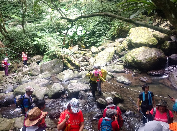 Guide helping hikers passing a creek